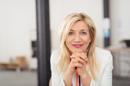 Happy attractive blond middle-aged woman with a friendly smile sitting resting her chin on her hands looking at the camera