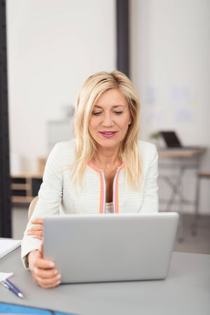 sitting down: Attractive stylish middle-aged blond businesswoman working on a laptop computer reading information on the screen with a serious expression