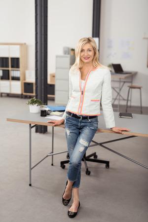 ragazze bionde: Figura intera sparato di una ragazza sorridente Bionda Ufficio donna pendente contro schiena su una scrivania con le gambe incrociate e guardando la camera.