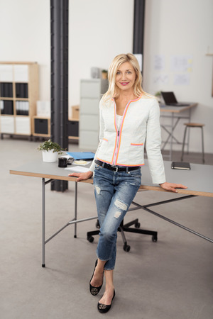 Full Length Shot of a Pretty Smiling Blond Office Woman Leaning Against her Back on a Desk with Legs Crossed and Looking at the Camera.