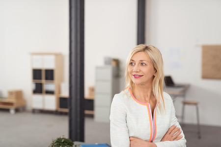 envisioning: Thoughtful Adult Blond Office Lady Looking Into Distance with a Smile While Crossing her Arms Over her Stomach. Stock Photo