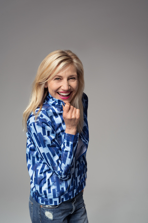 Cheerful Blond Adult Businesswoman Holding the Collar of her Blazer While Laughing at the Camera. Isolated on Gray Background.