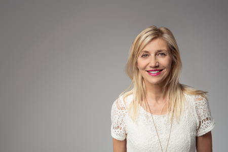 Close up Smiling Blond Adult Woman Looking at the Camera Against Gray Background with Copy Space for Texts