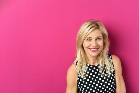 ragazze bionde: Close up Allegro Capelli biondi donna adulta su sfondo rosa con spazio di copia, sorride alla macchina fotografica.