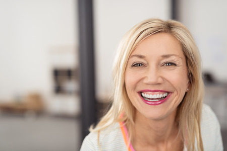 funny face: Laughing middle-aged blond woman with beaming smile looking directly into the camera Stock Photo
