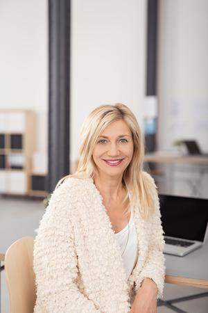 ragazze bionde: Close up Allegro adulto bianco biondo Ufficio donna che si siede su una sedia mentre Pendente contro la sua scrivania e guardando la camera.
