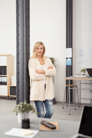 metal post: Confident Blond Office Woman Leaning Against Interior Metal Post with Arms Crossing Over her Stomach and Looking at the Camera. Stock Photo