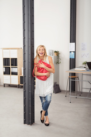 metal post: Full Length Shot of a Happy Young Blond Woman Embracing her Pink Bag While Leaning Against Indoor Metal Post in an Office. Stock Photo