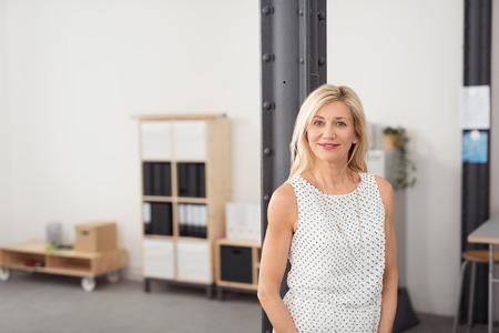 mujer sola: La mitad Shot Cuerpo de una Oficina de mujer adulta rubia en vestido sin mangas, posando dentro de la Oficina mientras sonriendo a la cámara