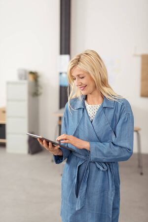 pleasure of reading: Happy attractive middle-aged blond businesswoman standing using a handheld tablet to surf the internet with a smile Stock Photo