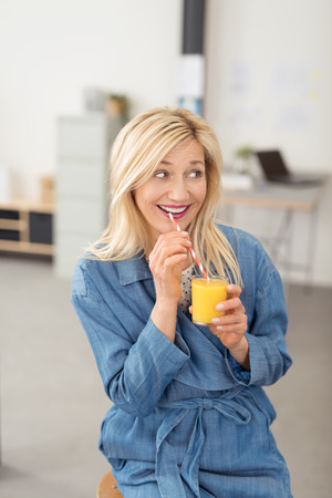 Playful woman enjoying a healthy glass of fresh orange juice looking to the side with a happy flirting smile