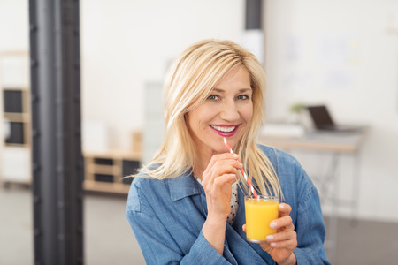 Attractive blond woman drinking a glass of freshly squeezed healthy orange juice looking at the camera with a friendly smile