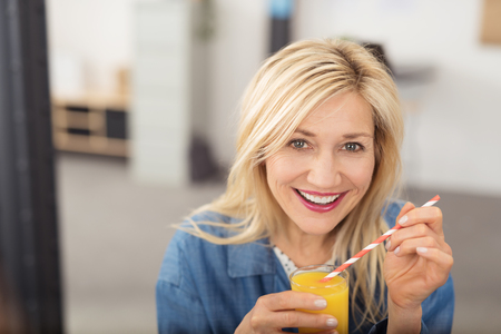 50s women: Healthy happy attractive middle-aged blond woman drinking fresh orange juice looking at the camera with a beaming smile Stock Photo