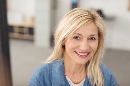 Long-haired blond woman with a joyful facial expression smiling at camera with blue eyes and white teeth, portrait indoors Stock Photo