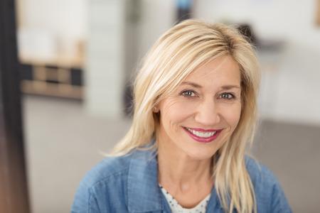 mujer alegre: Mujer rubia de pelo largo con una expresión facial alegre sonriendo a la cámara con ojos azules y blancos dientes, retrato en interiores Foto de archivo