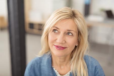 mujer pensando: Pensativo atractiva rubia mujer de mediana edad mirando hacia arriba en el aire con una sonrisa tranquila