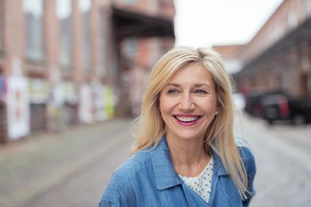 Zblízka šťastný dospělá žena s dlouhými blond vlasy, se smíchem při chůzi na ulici města