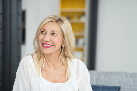 envisioning: Close up Thoughtful Blond Adult Office Woman in White Dress, Looking Up with a Toothy Smile. Stock Photo