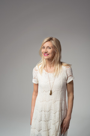 captured: Happy Portrait of a Blond Adult Woman, Wearing White Dress, Looking at the Against Gray Background. Captured in Studio. Stock Photo
