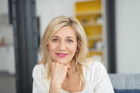Aantrekkelijke vrouw kijkt peinzend naar de camera met een rustige glimlach en haar kin op haar hand, binnenshuis thuis