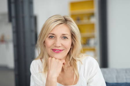 casual caucasian: Attractive woman looking pensively at the camera with a quiet smile and her chin resting on her hand, indoors at home