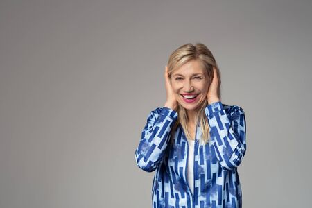 goofing: Portrait of a Happy Blond Businesswoman in Blue Blazer Covering her Ears with both Hands While Smiling at the Camera. Isolated on Gray Background with Copy Space.