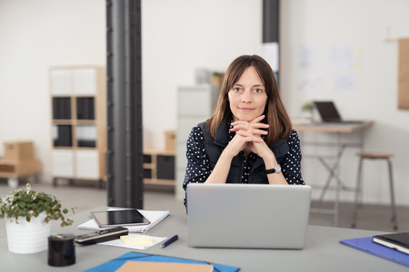 mujer pensativa: Oficina Mujer que se sienta en su escritorio con el ordenador portátil, apoyándose en sus manos en la Cruzada mientras sonriendo a la cámara.