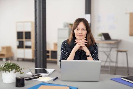 Oficina mujer sentada en su escritorio con ordenador portátil, apoyándose en sus manos cruzadas mientras sonríe a la cámara.