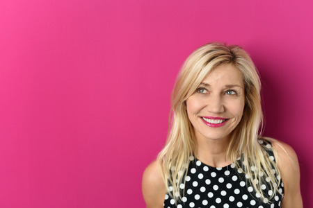 Close up Thoughtful Blond Adult Woman Looking up with a Smiling Facial Expression Against Pink Background with Copy Space