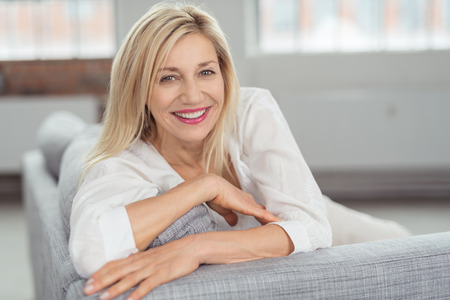 Close up Pretty Blond Adult Woman Sitting on Gray Couch, Looking at Camera with a Happy Facial Expression. Foto de archivo