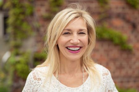 Radostné žena s blond vlasy po ramena při pohledu na fotoaparát s úsměvem šťastný zářící, venku s cihlové zdi a plazivými pozadí