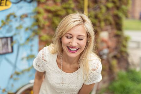 vivacious: Beautiful middle-aged blonde woman wearing laced white T-shirt while laughing and bending forward, outdoor portrait, in a warm day of spring or summer with green vegetation