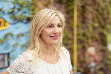 envisioning: Attractive middle-aged blonde woman with medium-length hair and white laced T-shirt looking away with a serene and jovial facial expression, outdoors, in front of a wall with green climbing plants