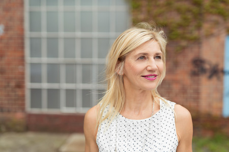 Stylish blond woman in a white summer top standing watching something in the air to the right of the frame, outdoors against a brick building Reklamní fotografie