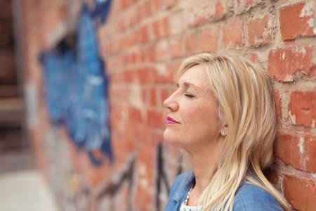 mujer sola: Mujer joven atractiva que se relaja la espalda apoyada en una pared de ladrillos con los ojos cerrados mientras se toma un momento para s� misma, vista de perfil