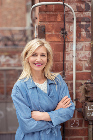 Confident friendly blond woman with a charming smile standing with her arms folded leaning on a brick wall smiling at the camera photo