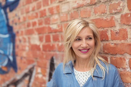 femme chatain: Close up Heureux Adulte Femme avec Cheveux blonds appuy� contre Vieux Mur de briques tout en regardant dans Distance.