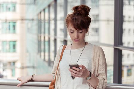 젊은 여자가 고층 도시 건물의 배경으로 그녀의 휴대 전화에 SMS 또는 문자 메시지를 확인하기 위해 일시 중지