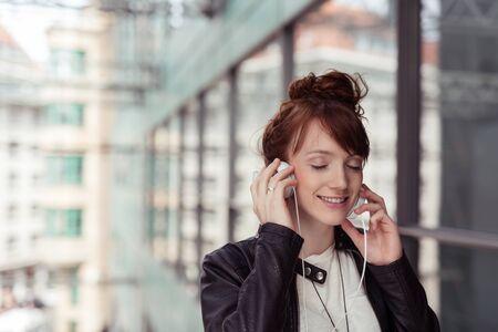 audifonos: Pensativo mujer bastante joven en chaqueta de cuero Negro, Escuchar música con auriculares con los ojos cerrados y una cara sonriente.