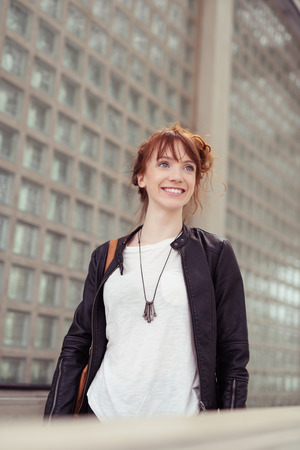 Smiling Confident Young Woman with Red Hair Dressed Casually and Walking Past Urban Architecture photo