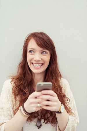 clasping: Pretty young redhead woman beaming with delight and happiness as she looks up while clasping her mobile phone in both hands