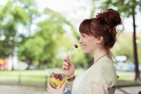 botanas: Vista lateral de una mujer sonriente bastante joven en el parque, que come la ensalada de fruta fresca en un envase de plástico mientras mira a Distancia.