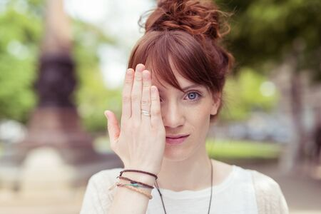 women face stare: Attractive redhead woman holding her hand to her eye and looking at the camera with a serious expression as she stands outdoors in an urban park Stock Photo