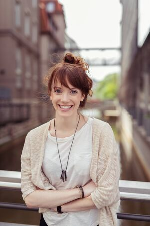 Close up Smiling Young Woman in Casual Clothing, Leaning Against the Bridge Railings with Arms Crossing Over her Stomach, Looking at the Camera with a Toothy Smile.
