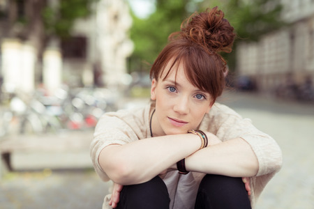 knees bent: Young redhead woman sitting with her chin on her hands resting on her bent knees staring intently at the camera with a pensive expression