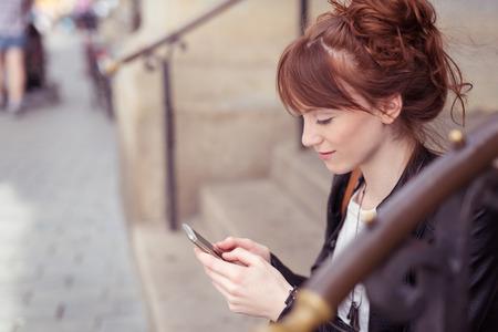 personas comunicandose: Mujer bonita que se sienta en los escalones en una calle urbana de leer un sms en su teléfono móvil, el perfil de vista Foto de archivo