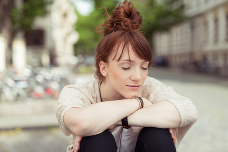 bent over: Young woman relaxing in a urban square sitting with her head resting on her arms over her bent knees with her eyes closed and a serene expression