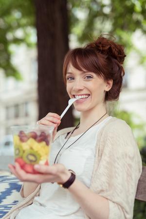 ensalada de frutas: Mujer feliz que come fresca ensalada de frutas con frutas tropicales exóticas mientras se relaja la sombra de un árbol en un parque Foto de archivo