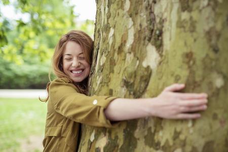 Muy feliz adolescente rubio Muchacha que abraza el enorme tronco de árbol en el parque con los ojos cerrados y la sonrisa con dientes. Foto de archivo