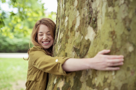 personas abrazadas: Muy feliz adolescente rubio Muchacha que abraza el enorme tronco de árbol en el parque con los ojos cerrados y la sonrisa con dientes.